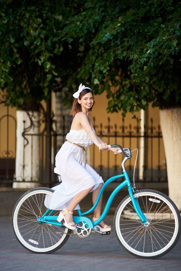 Den skämtsamma kvinnlign på tappningcykeln rider längs stadsgatan arkivbilder
