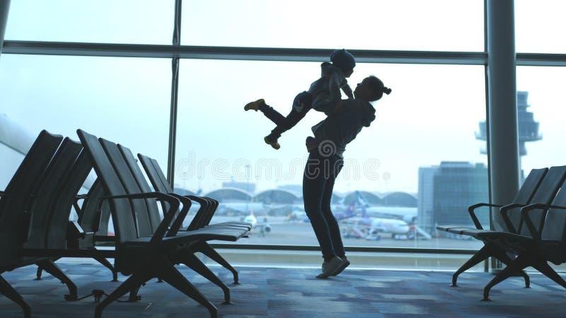 Den skämtsamma modern lyfter hennes son och rymmer honom i armar som ser till och med fönster i flygplats arkivfoton