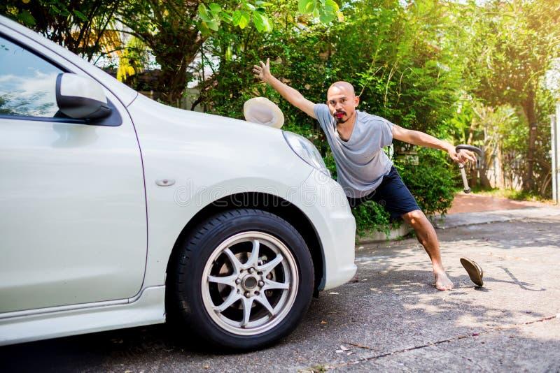 Den skalliga asiatiska mannen sloggs av en vit bil framme av hans hus arkivfoto