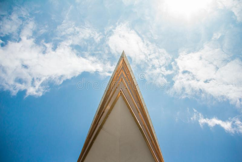 Den skarpa tornspiran av byggandet klipper igenom molnen arkivfoton