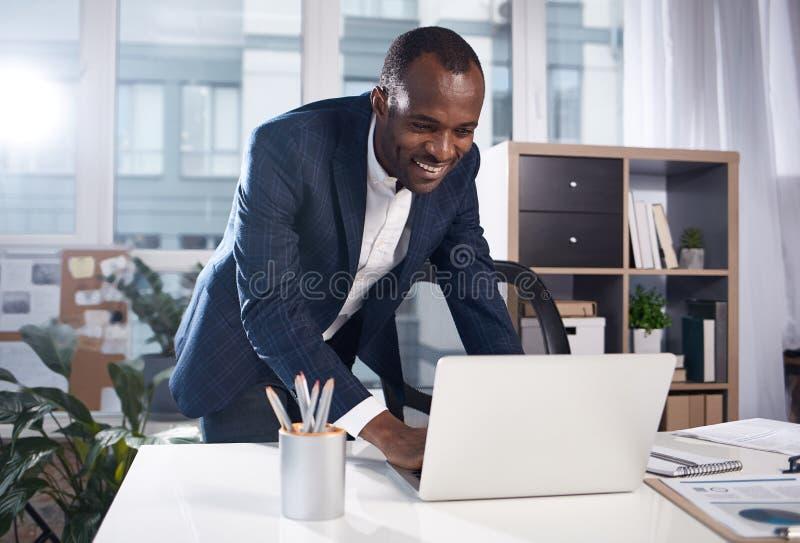 Den skickliga glade chefen arbetar med nöje arkivfoto