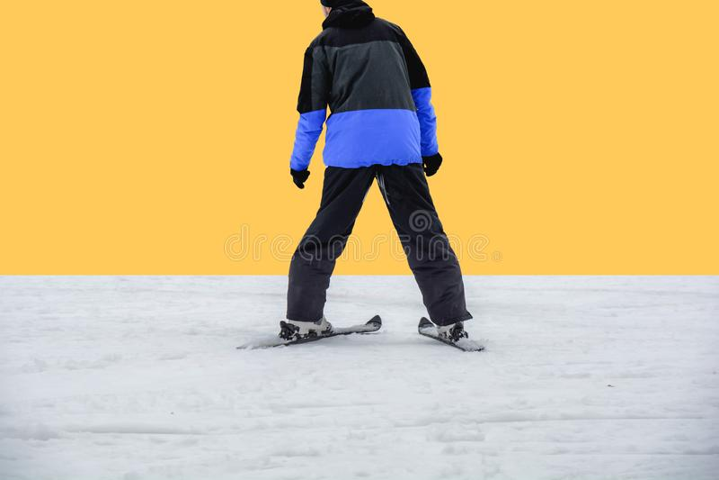 Den skida mannen skidar på i omslaget som är klart för att skida på guling royaltyfri fotografi