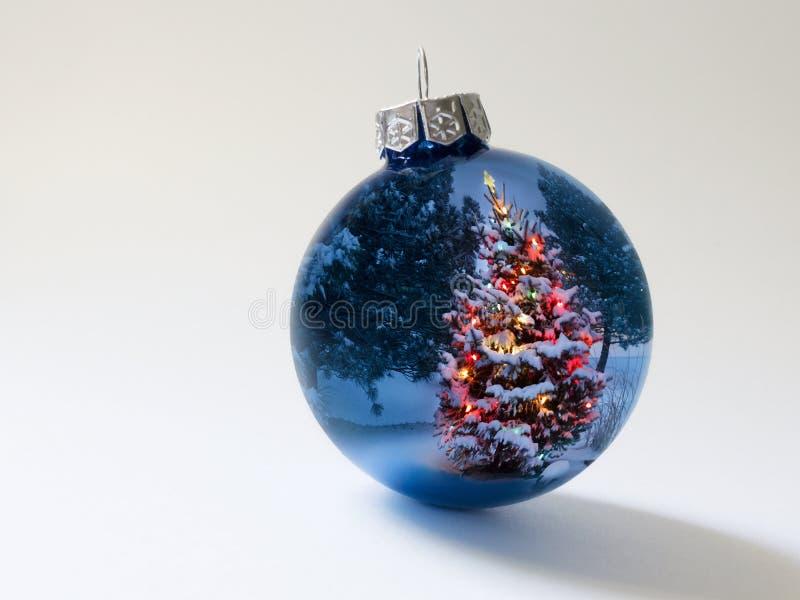 Den skinande blåttferieprydnaden reflekterar ljust den färgrika julgranen för liten arkivbild