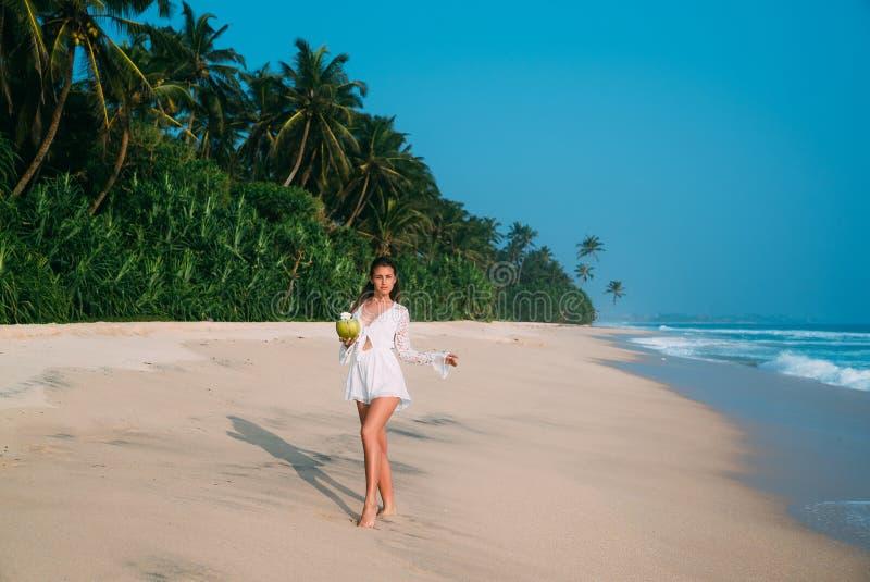 Den skinande brunbrända flickan i en moderiktig stranddräkt som strosar längs kusten, flög för att vila på dvalan Begreppet av royaltyfria bilder