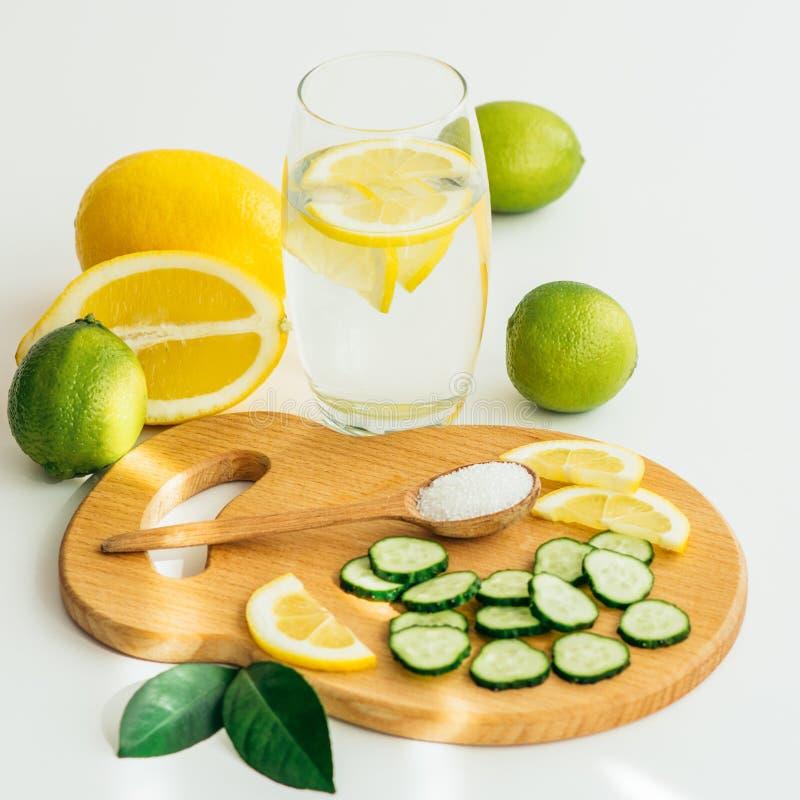 Den skivade gurkan och apelsinen, en sked med saltar och ett exponeringsglas med vatten och citronen arkivbild