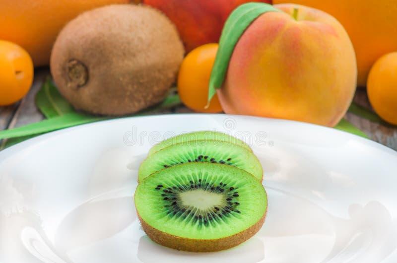 Den skivade kiwin på en vit platta och annan bär frukt royaltyfri foto