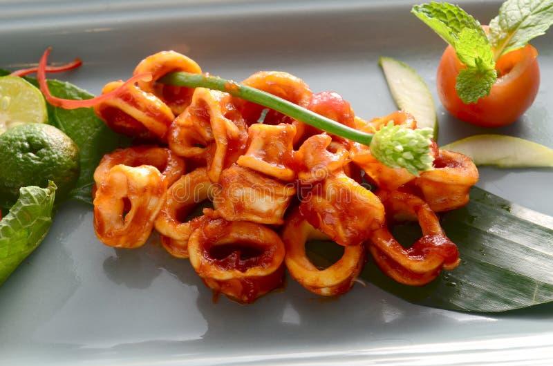 Den skivade tioarmade bläckfisken besegrar extra kryddig sås, den röda tioarmade bläckfisken och limefrukt och nya tomater royaltyfri fotografi