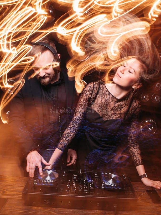 Den skivajockeyn och blondinen tycker om musik på nattklubben arkivbild