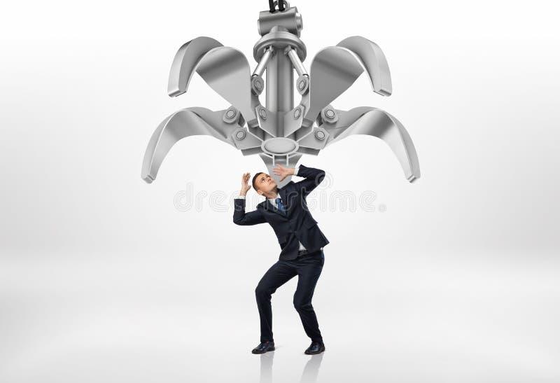 Den skrämda affärsmannen i skyddande poserar att se upp på den jätte- mekaniska jordluckraren ovanför honom royaltyfri illustrationer