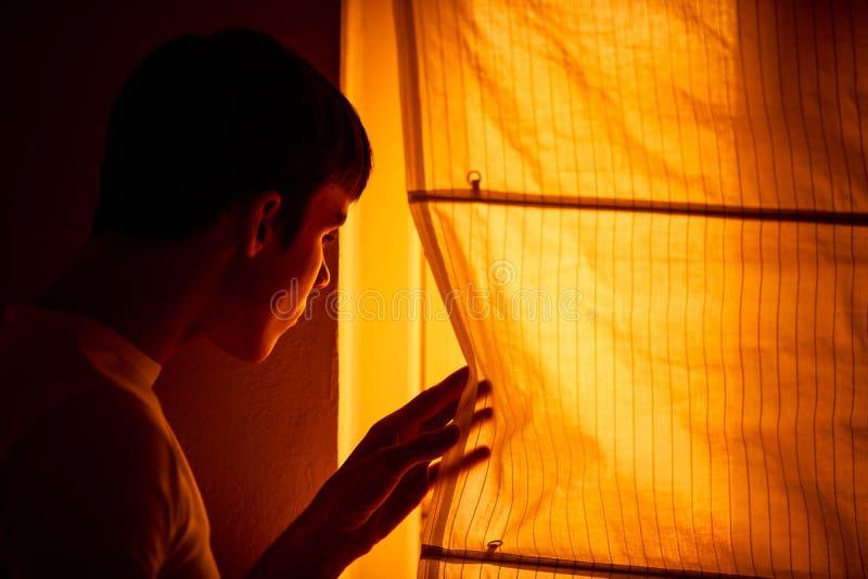 Den skrämda unga mannen står bredvid fönster arkivbild