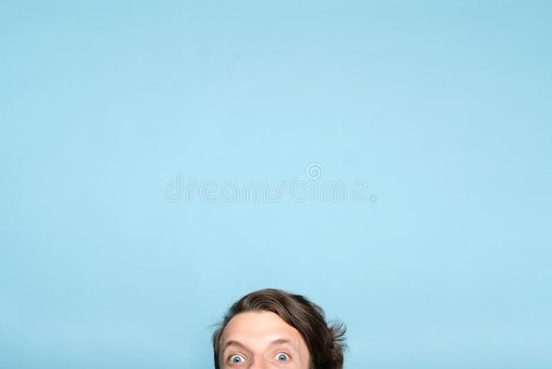 Den skrämde excentriska mannen som ler ögon, kikar ut nedersta arkivbild