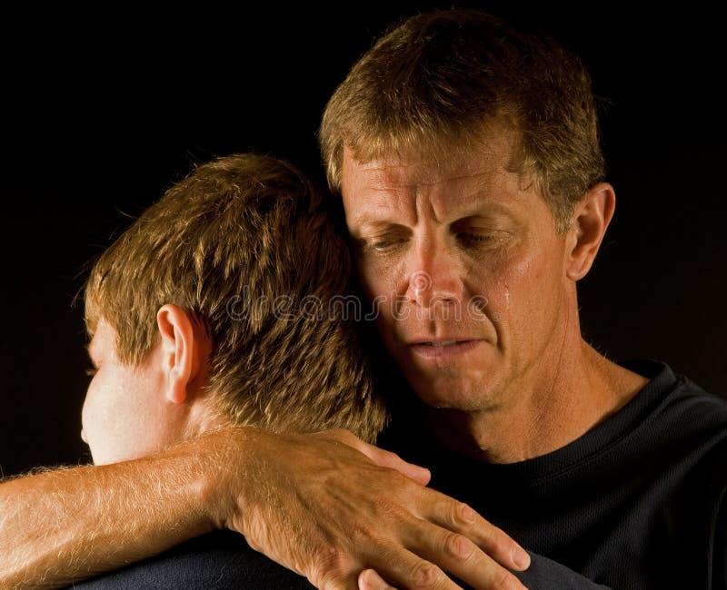 den skriande fadern kramar sonen arkivbilder