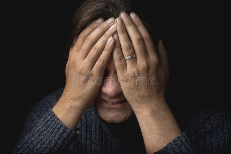 Den skriande mannen lider och täcker hans framsida med händer Fördjupningen som är mental smärtar, tragedin, problem i liv och so royaltyfri bild