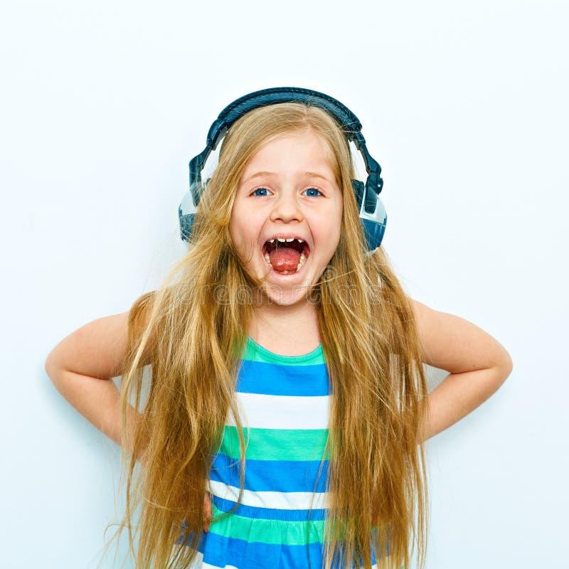 Den skrikiga lilla flickan med den roliga ståenden för hörlurar isolerade nolla fotografering för bildbyråer