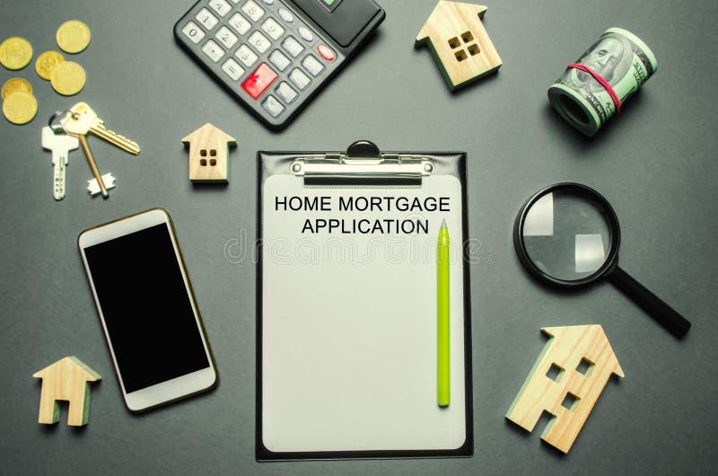 Den skrivbordfastighetsmäklaren och minnestavlan med ordhemmet intecknar applikation Egenskapslån Lån för en lägenhet eller ett h fotografering för bildbyråer