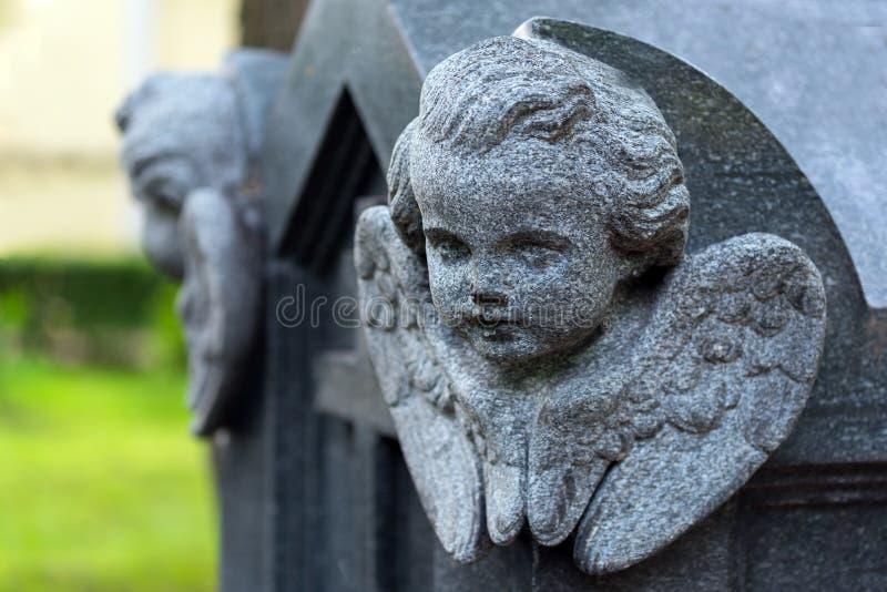 Den skulpturala bilden av en ängel sned på en granit arkivbilder