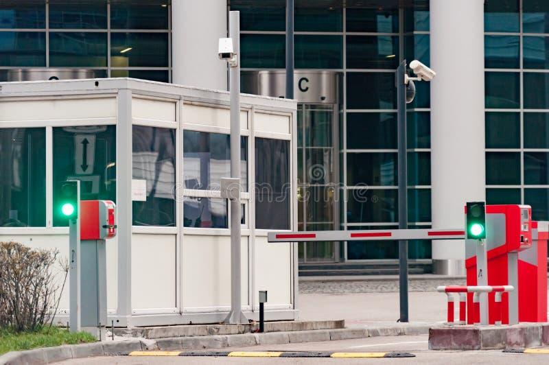 Den skyddande barriären och säkerhetskontoret på ingången till kontorsparkeringsplatsen royaltyfria foton