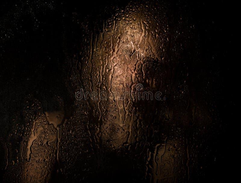 Den släta ståenden av den sexiga modellen som poserar bak genomskinligt exponeringsglas som täckas av vatten, tappar ung melankol arkivbild