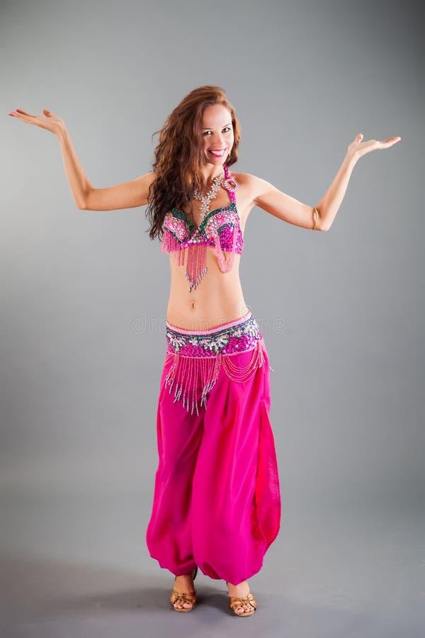 Den slanka flickan i dräkt för den lilaOrient dansen poserar royaltyfri bild