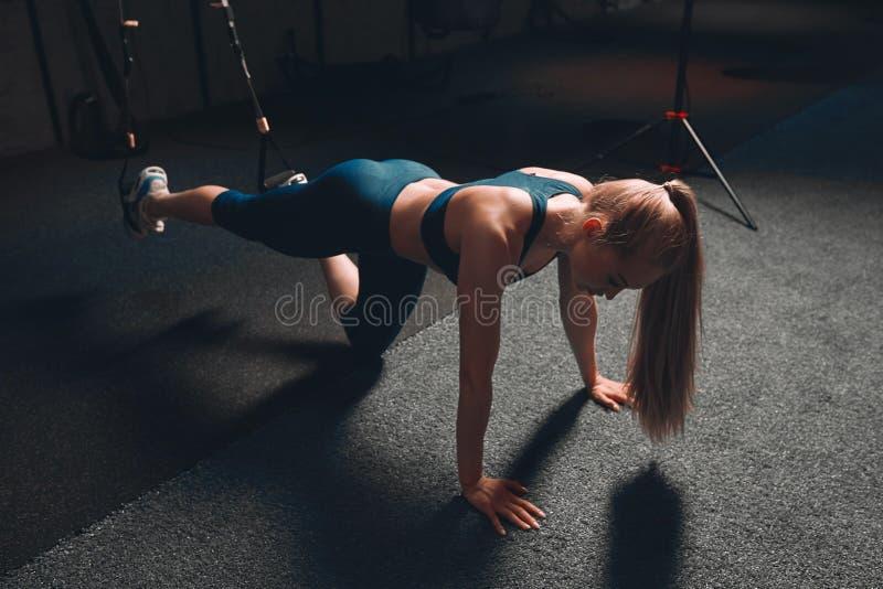 Den slanka flickan som lutar på golvet med plams som, att utföra skjuter, ups arkivfoto