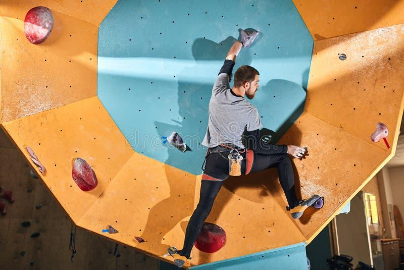 Den slanka fysiskt utmanade idrottsmannen som flyttar sig upp på konstgjort, vaggar väggen royaltyfri foto