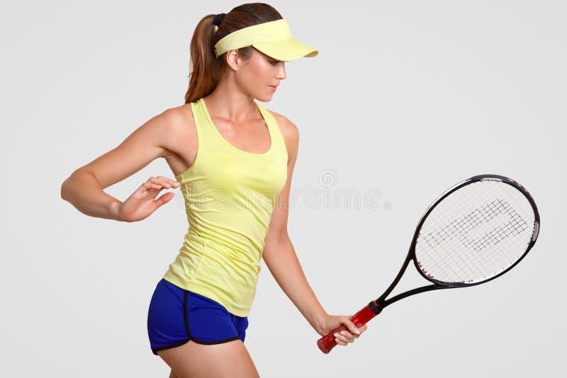 Den slanka sportiga kvinnan motiverar sig på leken, rymmer tennisracket, har stridighetande, önskar att visa briljant kapacitet,  fotografering för bildbyråer