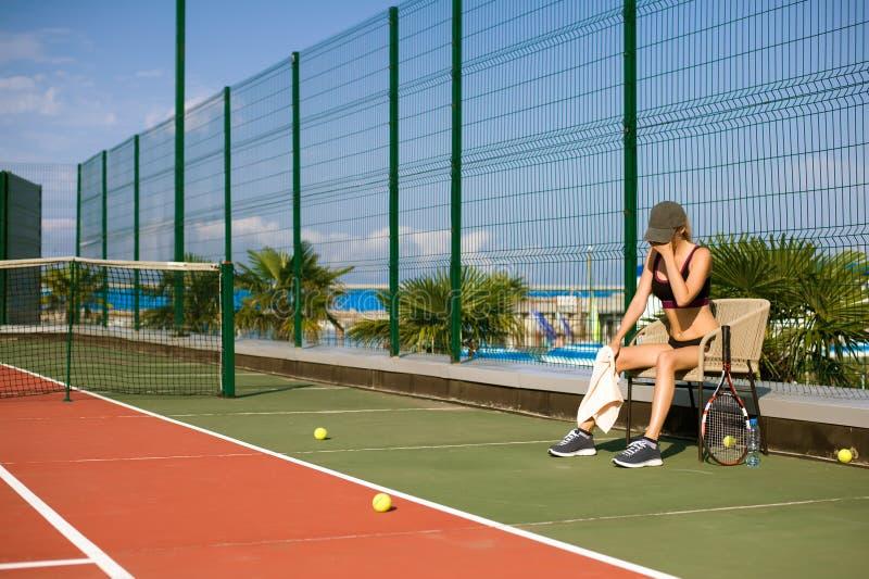 Den slanka ung flickaidrottsman nentennisspelaren är på den öppna tennisbanan i sommar royaltyfri foto