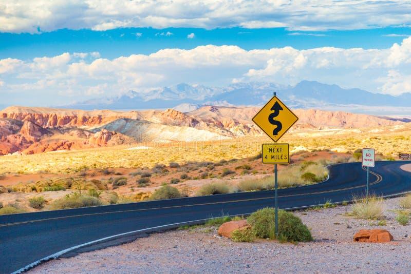 Den slingriga vägen med undertecknar in dalen av branddelstatsparken, Nevada arkivbild