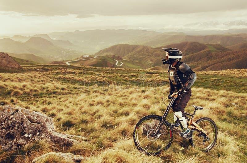 Den sluttande ryttaren på en mountainbike i en mountainbike rider längs vägen i natur mot bakgrunden av berget royaltyfria foton