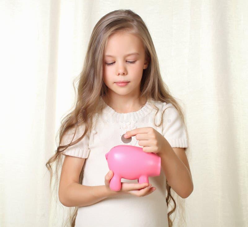 Den små blonda flickan sätter myntet in i piggy moneybox fotografering för bildbyråer