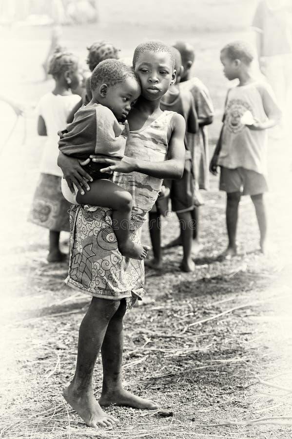 Den små systern rymmer henne brodern i Ghana royaltyfria foton