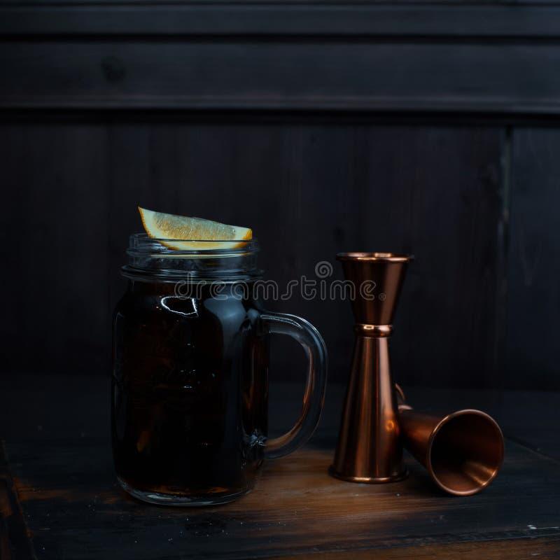 Den smakliga alkoholiserade coctailen med is, svart rom och coca-cola, citronskivor står på en trätabell i en restaurang royaltyfri fotografi
