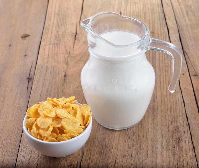 Den smakliga cornflakens i den vitt bunken och exponeringsglas av mjölkar royaltyfria bilder