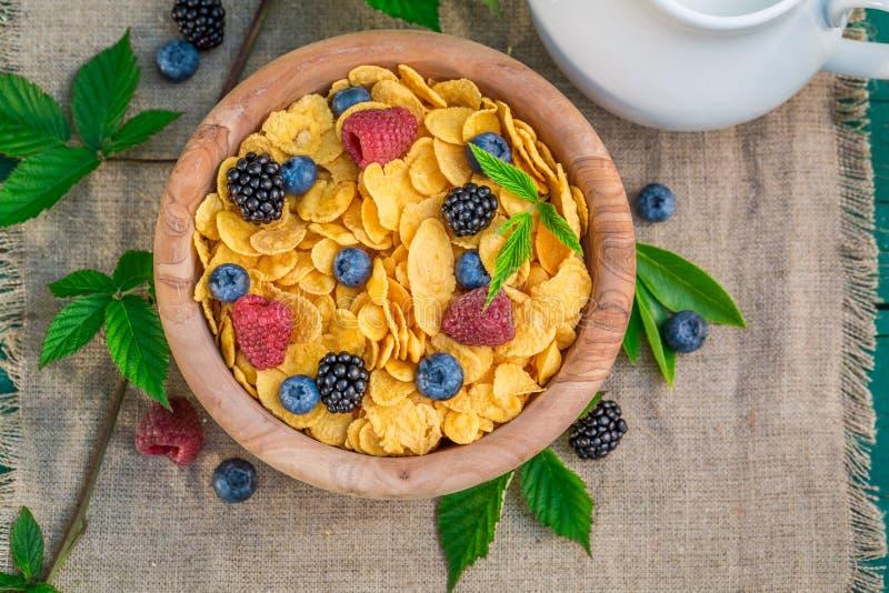 Den smakliga cornflakens med bärfrukter och mjölkar arkivbilder