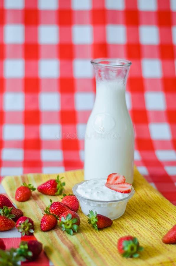 Den smakliga frukosten som är ny mjölkar i glasflaskan, smaklig yoghurt i liten glass bunke med många jordgubbar omkring royaltyfri bild