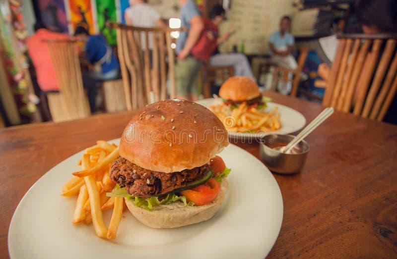 Den smakliga hamburgaren med fransmansmåfiskar och såser tjänade som på tabellen av ett fullsatt snabbmatkafé Matställe, frukost  royaltyfri foto