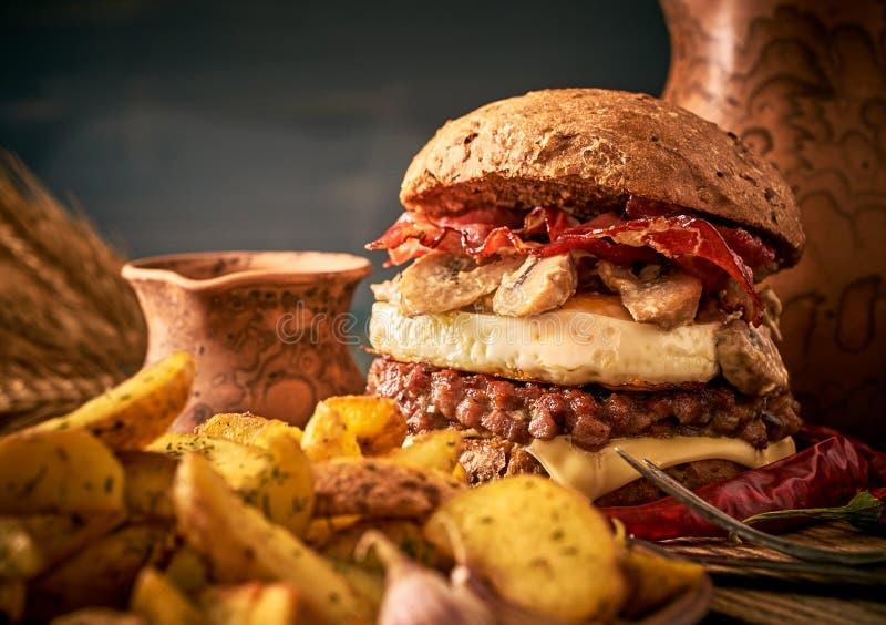 Den smakliga hamburgaren med nötkött, bacon, stekte ägget och champinjoner royaltyfri bild