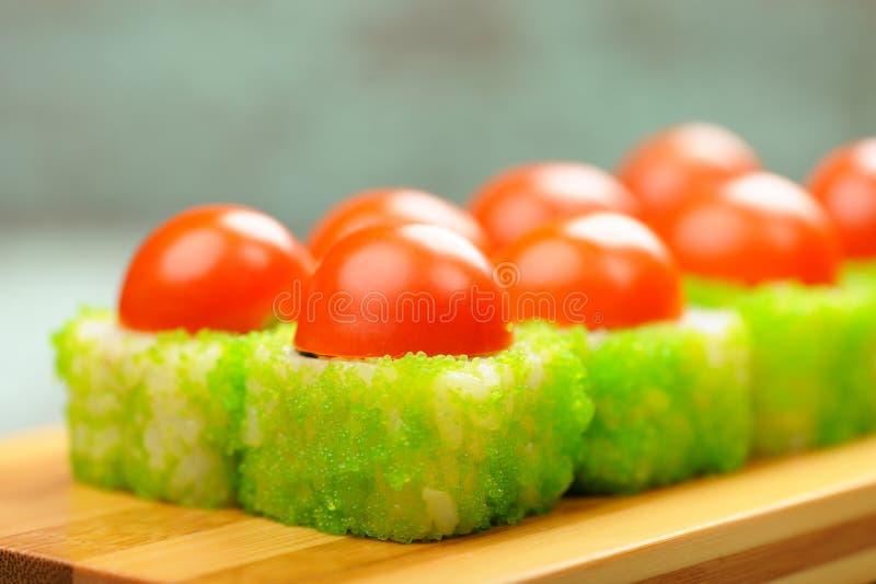 Den smakliga japanska fantasin rullar med körsbärsröda tomater och grön cavi arkivfoton
