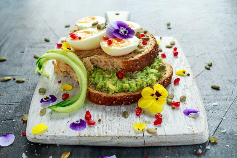 Den smakliga smörgåsen med avokadot kokade ägg, pumpa kärnar ur, och den ätliga altfiolen blommar i ett vitt bräde sund mat fotografering för bildbyråer