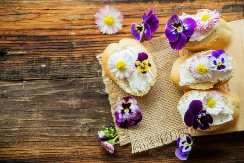Den smakliga smörgåsen med avokadot kokade ägg, pumpa kärnar ur, och den ätliga altfiolen blommar i ett vitt bräde sund mat arkivfoton