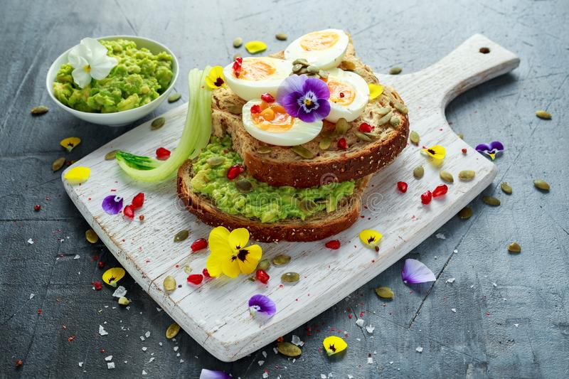 Den smakliga smörgåsen med avokadot kokade ägg, pumpa kärnar ur, och den ätliga altfiolen blommar i ett vitt bräde sund mat royaltyfri bild