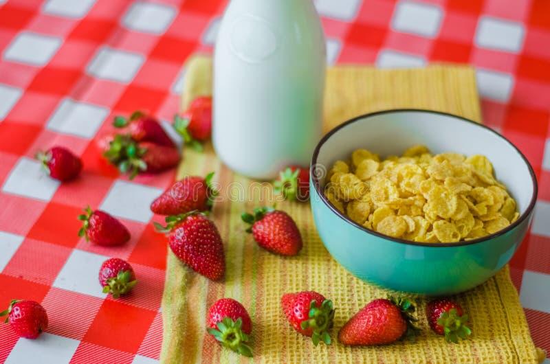 Den smakliga sunda frukosten som är ny mjölkar i glasflaska, sädesslag med honung och muttrar i grön keramisk bunke och smaklig y royaltyfri bild