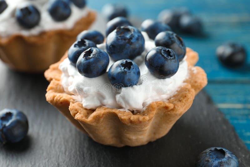 Den smakliga tartleten med blåbär kritiserar på plattan, closeup fotografering för bildbyråer