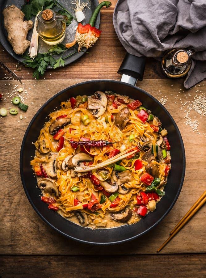 Den smakliga vegetarian stekte nudelpannan med grönsaker och krämig pastasås på träbakgrund royaltyfri fotografi