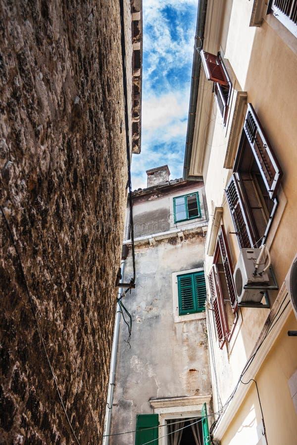 Den smala gatan i staden med gamla byggnader royaltyfri bild