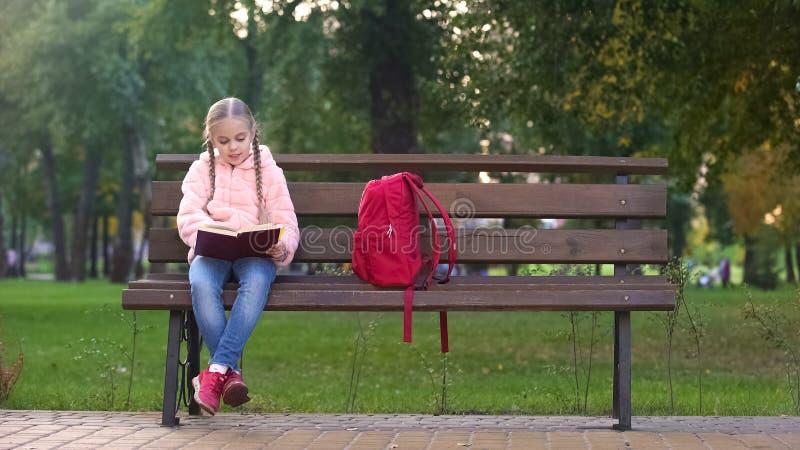 Den smarta flickaläseboken parkerar in på bänken, den intellektuella hobbyen som spenderar fri tid royaltyfria foton
