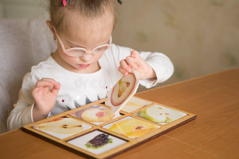 Den smarta flickan med Down Syndrome samlar pussel royaltyfri bild