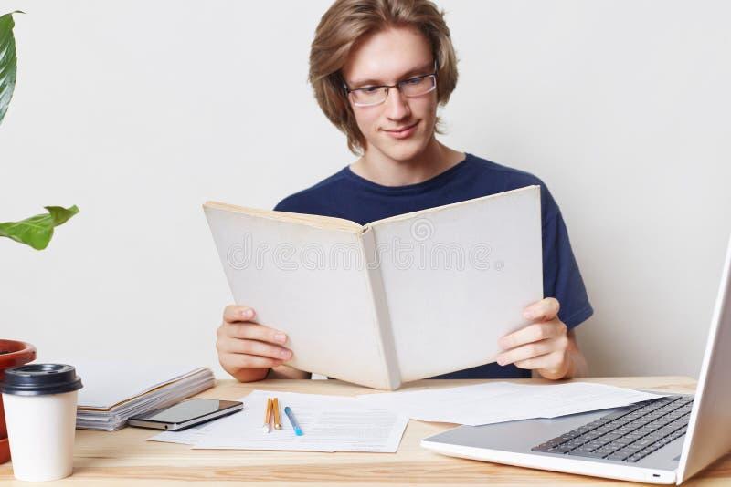 Den smarta hårda funktionsdugliga stilfulla manliga studenten bär anblickar, har uppmärksam blick i bok, läser vetenskaplig litte arkivfoton