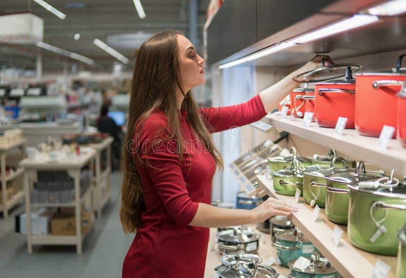 Den smarta hemmafrukvinnan köper en kastrull i supermarket royaltyfri foto