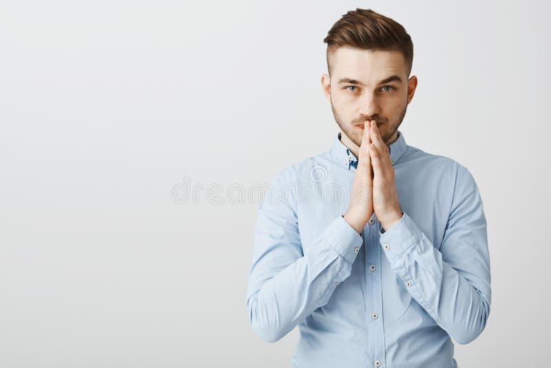 Den smarta idérika ambitiösa stiliga mannen med borstet i stilfulla formella skjortainnehavhänder ber in över mun i snille royaltyfria foton
